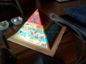 Polychroom 24 cm pyramid orgonite, bijenwas, polychroom jaspis, bergkristal met zwarte tourmalijn, metalen, andere materialen.